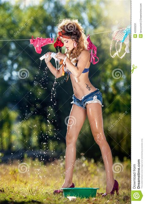 Brunette Woman In Bra And Denim Shorts Putting Clothes To